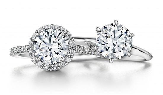 halo engagement ring and solitaire engagement ring stacked on top of each other